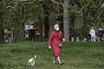 28-03-2020 - Coronavirus Pandemic, Elderly woman walking the dog wearing disposable gloves and face mask, Barnes, London © Duncan Phillips