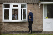 31-03-2020 - Coronavirus Pandemic. Conversation through an open window. Man talking to an elderly woman maintaining social distance during the lockdown © John Harris