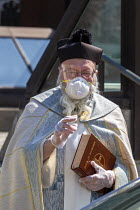 11-04-2020 - Grosse Pointe Park, Michigan USA Coronavirus pandemic. Priest giving the traditional blessing of the Easter baskets. Wearing a mask, face shield, disposable gloves and maintaining correct social dista... © Jim West
