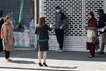 16-04-2020 - Coronavirus Pandemic. Bank worker helping customers to maintain social distance in the queue outside Lloyds Bank, King's Heath, Birmingham © John Harris