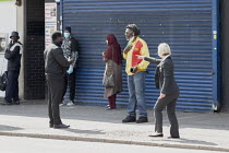 16-04-2020 - Coronavirus Pandemic. Argument betwen customer and bank worker helping customers to maintain social distance in the queue outside Lloyds Bank, King's Heath, Birmingham © John Harris