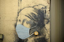 04-22-2020 - Coronavirus Pandemic. The Girl with a Pierced Eardrum by Banksy modified with a face mask added, Bristol Harbourside. Parody of The Girl With The Pearl Earring by Dutch painter Johannes Vermeer © Sam Morgan Moore