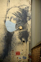 22-04-2020 - Coronavirus Pandemic. The Girl with a Pierced Eardrum by Banksy modified with a face mask added, Bristol Harbourside. Parody of The Girl With The Pearl Earring by Dutch painter Johannes Vermeer © Sam Morgan Moore