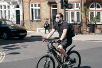 22-04-2020 - Coronavirus Pandemic. Cyclist wearing face mask, Central London © Duncan Phillips