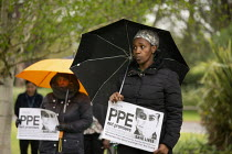 28-04-2020 - Minute's silence for key workers who have died in the Coronavirus Pandemic, Health workers at Warneford Hospital, Oxford, Placards demanding PPE not promises, International Workers Memorial Day © John Harris
