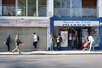 15-04-2020 - Coronavirus Pandemic. Shoppers queuing maintaining social distance 24 hour Pharmacy, Barnes, London © Duncan Phillips