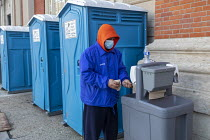 01-05-2020 - Detroit, Michigan USA. Coronavirus Pandemic. Homeless man using an outdoor handwashing station, Pope Francis Center. The Center has had to close its indoor spaces due to the. It is now serving meals o... © Jim West