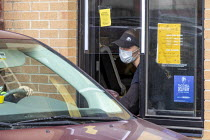 08-05-2020 - Michigan, USA. Taco Bell worker delivering an order at the drive through window. Due to the coronavirus pandemic, customers are not allowed inside the fast food restaurant. Workers at this restaurant... © Jim West