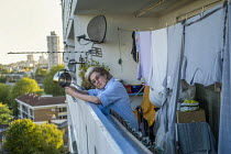 14-05-2020 - Helen bangs her sausepan from a tower block during a Thursday night clap for carers and the NHS during Covid 19, Tower Hamlets, East London. © Jess Hurd