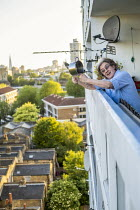 14-05-2020 - Coronavirus Pandemic. Clap for our Carers, Helen banging a saucepan, tower block, Tower Hamlets, East London © Jess Hurd