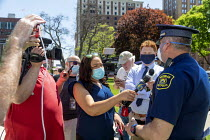 20-05-2020 - Lansing, Michigan USA Coronavirus Pandemic rally, journalists interviewing a State Police spokesperson during rally on the lawn of the Michigan State Capitol in protest at emergency orders which keep... © Jim West