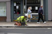 05-15-2020 - Coronavirus Pandemic. Worker repairing pavement as pedestrians walk by, closed shops, Stratford Upon Avon © John Harris