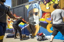 25-05-2020 - Coronavirus Pandemic: NHS heroes graffiti artist Owe1 painting a mural depicting health worker in PPE, Shoreditch, East London. © Jess Hurd