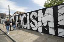 09-06-2020 - Plain clothes police unit walk past United Aganst Racism graffitii, Brick Lane, East London © Jess Hurd