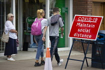 16-06-2020 - Elderly woman looking at young couple, Maintain Social Distance sign, Stratford Upon Avon © John Harris