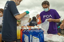 27-06-2020 - Detroit, Michigan USA Volunteers from FCA distributing food, masks, sanitizer and other necessities to 100s of people during the coronavirus pandemic. The corporation is building a new vehicle assembl... © Jim West