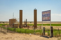 03-07-2020 - Colorado, USA. Support Your Local Rnacher Buy U.S.A. Beef sign. Farm silos and oil storage tanks. Oil development has allowed many family farms to continue operating. But that oil boom is now threaten... © Jim West