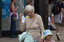 24-07-2020 - Mask up Friday, Shoppers removing her mask on leaving a shop, Stratford Upon Avon. Grandmother and child. © John Harris