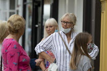 24-07-2020 - Mask up Friday, shoppers with masks talking as they wait in line in the street, Stratford Upon Avon © John Harris