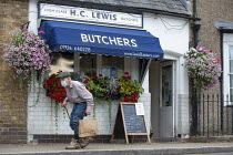 01-08-2020 - Elderly man with stick and face mask shopping at H C Lewis Butchers, Kineton, Warwickshire © John Harris