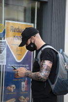 29-07-2020 - Customer with face mask, tattoos checking his phone whilst queuing, Greggs bakery Stratford Upon Avon © John Harris