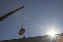 02-07-2020 - Denver, USA: Workers installing solar panels on the roof of new affordable housing building. Lifting equipment for a solar energy installation to the top of a new affordable housing building. The sola... © Jim West