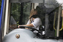 05-08-2020 - Woman bus driver, rural route, Warwickshire. Check mirrors before pulling out from a village bus stop © John Harris