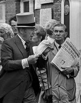 16-06-1975 - Royal Ascot races 1975 striking stable lads picketing. Bad news from Italy for a harrassed racegoer arriving in top hat and morning dress. Ascot racecourse, Berkshire © Martin Mayer