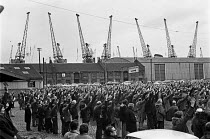 18-12-1971 - London dockers voting, mass meeting 1971. Dock cranes and warehouses © NLA