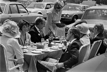 19-06-1979 - Royal Ascot races 1979 enjoying champagne lunch, wealthy picnicking in the car park and being served by a servant © NLA