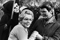 09-11-1983 - Margaret Thatcher and Ronald Reagan (in masks) 1983, US Embassy, London, makeing merry while death stalks behind. Greenham Common women protest © Peter Arkell
