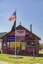 16-08-2020 - Three Oaks, Michigan, USA, home covered with pro Trump signs, 2020 presidential election campaign. Donald Trump supporter has put up Stars and Stripes flag and a Liberty Bell. Trump as superhero and t... © Jim West