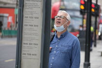 18-08-2020 - Man with mask reading a bus stop timetable. Shoppers, Oxford Street, London. Easing of Covid-19 lockdown restrictions. © Philip Wolmuth
