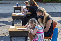 27-08-2020 - Michigan, USA, First day of school, socially distanced orientation for parents and pupils, St. Clare of Montefalco Catholic School. Students and parents sign a document promising to wear face masks an... © Jim West