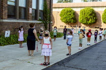 27-08-2020 - Michigan USA. First day of school, teacher helping pupils practice lining up six feet apart, St. Clare of Montefalco Catholic School. The school has a diverse student body from Grosse Pointe and Detro... © Jim West