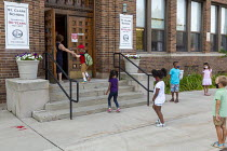 27-08-2020 - Michigan, USA, First day of school, pupils entering St. Clare of Montefalco Catholic School six feet apart. The school has a diverse student body from Grosse Pointe and Detroit. © Jim West