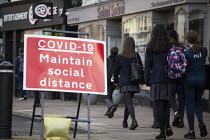 10-11-2020 - Pupils walking home by Covid-19 Maintain Social Distance sign, Stratford Upon Avon, Warwickshire © John Harris