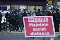 10-11-2020 - Pupils socialising, bus stop by Covid-19 Maintain Social Distance sign, Stratford Upon Avon, Warwickshire. Faces blurred © John Harris