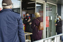24-11-2020 - Customers being served at the door, Argos, Maybird Shopping Centre, Stratford upon Avon, Warwickshire. Shopworker serving through the front door to a socially distanced queue of shoppers © John Harris
