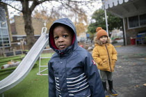 27-11-2020 - Nursery children playing outside in their bubbles, Lansbury Lawrence Primary School during Covid pandemic lockdown, Poplar, East London. Slide in the playgound © Jess Hurd