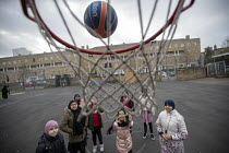 27-11-2020 - Shooting basketball hoops, breaktime in the playground, Lansbury Lawrence Primary School during Covid pandemic lockdown, Poplar, East London. © Jess Hurd