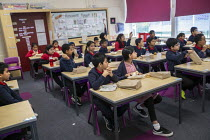 27-11-2020 - Dinner alternates between packed lunch in the classroom and hot lunch, as part of Covid measures. Lansbury Lawrence Primary School during Covid pandemic lockdown, Poplar, East London. © Jess Hurd