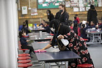 27-11-2020 - Dinner staff wearing face masks cleaning tables between each bubble. Lansbury Lawrence Primary School during Covid pandemic lockdown, Poplar, East London. © Jess Hurd