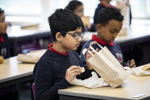 27-11-2020 - Lunch alternates between packed lunch in the classroom and hot lunch, as part of Covid measures. Lansbury Lawrence Primary School during Covid pandemic lockdown, Poplar, East London. © Jess Hurd