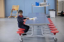 27-11-2020 - Last pupil to finish lunch in a class bubble, Lansbury Lawrence Primary School during Covid pandemic lockdown, Poplar, East London. © Jess Hurd