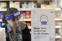 05-12-2020 - Pharmacist wearing face shield serving a customer, a protective perspex screen is across the counter, Pharmacy, Bristol © Paul Box