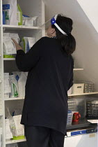 05-12-2020 - Pharmacist finding a customer prescription wearing face shield, Pharmacy, Bristol © Paul Box
