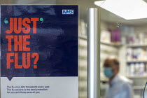 05-12-2020 - NHS Flu vaccine sign on a protective perspex screen across the counter, Pharmacy, Bristol © Paul Box