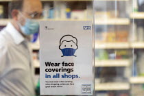 05-12-2020 - Sign requiring customers to wear a face covering in all shops, Pharmacy, Bristol. Pharmacist serving a customer wearing face shield with a protective perspex screen across the counter © Paul Box