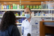 05-12-2020 - Pharmacist serving a customer wearing face mask, with a protective perspex screen across the counter, Pharmacy, Bristol © Paul Box